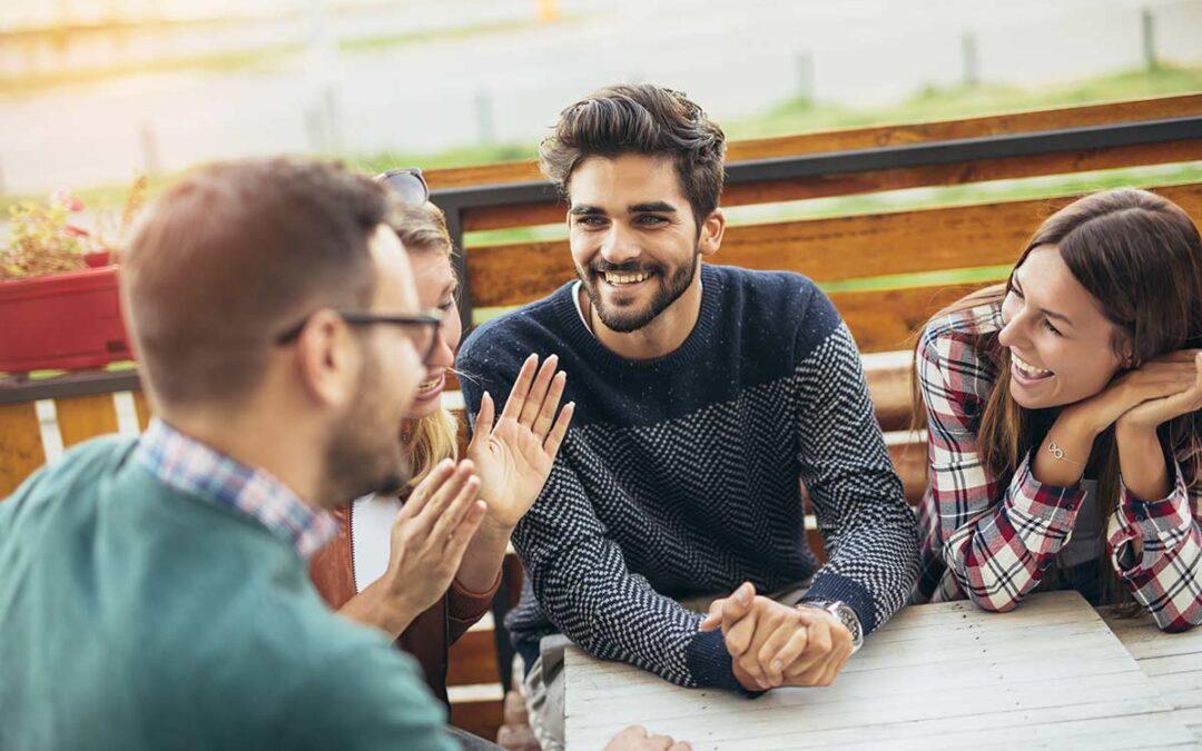 Groupe d'hommes et de femmes réunis autour de la table