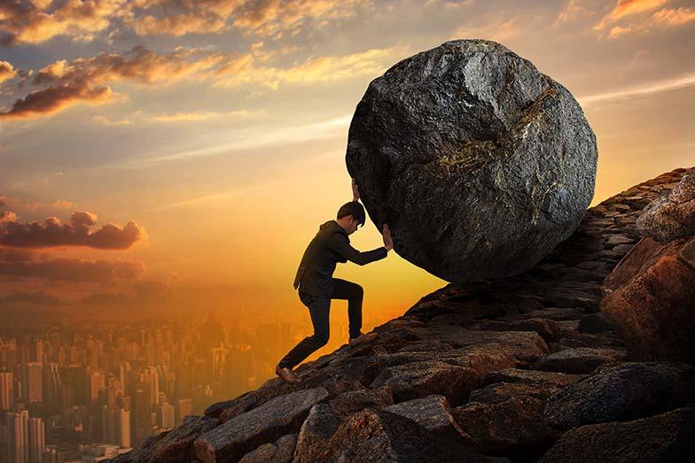 Homme poussant un énorme rocher en montée